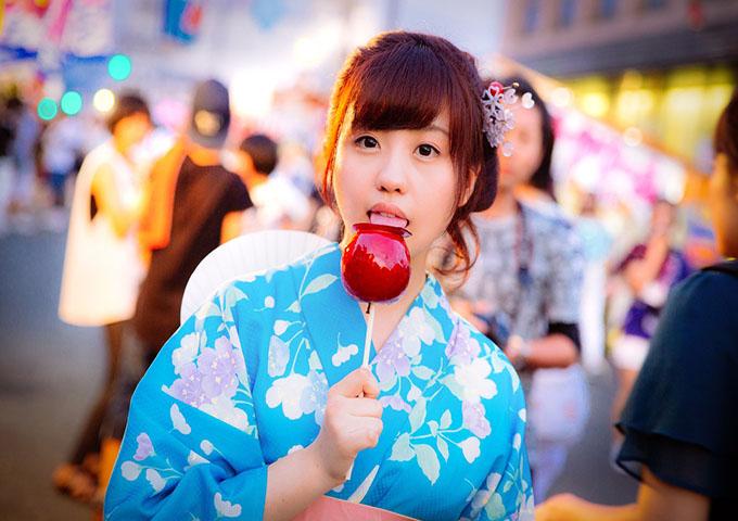 祭りりんごあめを食べる女性